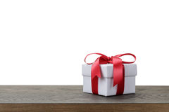 Gift box with red bow on rustic table Royalty Free Stock Image
