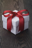 Gift box with red bow on rustic table Stock Photos