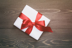 Gift box with red bow on rustic table Stock Images