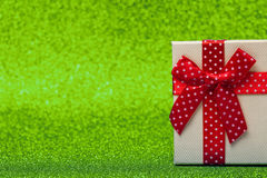 Gift box with red bow on sparkling green background. Bright and festive. Royalty Free Stock Image