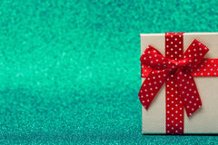 Gift box with red bow on sparkling green background. Bright and festive. Stock Images