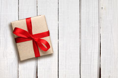 Gift box with red bow on white wood Stock Images