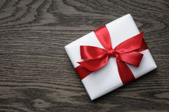 Gift box with red bow on wood table Stock Photos