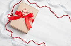 Gift box with red bow on wooden table. Christmas background with festive decoration. Place for your text. copyspace. top Stock Photography