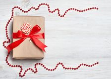 Gift box with red bow on wooden table. Christmas background with festive decoration. Place for your text. copyspace. top view, fla Royalty Free Stock Photo
