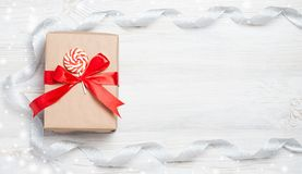 Gift box with red bow on wooden table. Christmas background with festive decoration. Place for your text. copyspace. top Stock Images