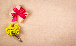 Gift box with a red bow and yellow flowers. Romantic concept. Backgrounds and textures. Copy space Stock Photography