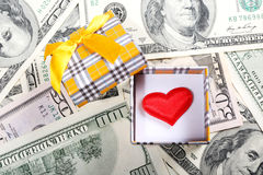 Gift box with red heart on money background Royalty Free Stock Photography