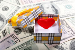 Gift box with red heart and money, close up Royalty Free Stock Photography