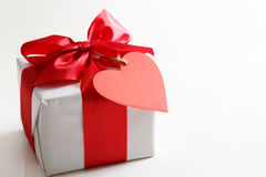 Gift box with red heart tag. Gift box with red satin ribbon and heart tag Stock Images
