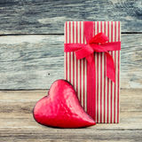 Gift box and red heart on wooden background , vintage style. Copy space. Valentines day background Royalty Free Stock Images