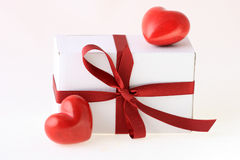 Gift box and red hearts Stock Image