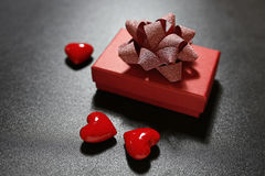 Gift box with red hearts on black background Royalty Free Stock Image