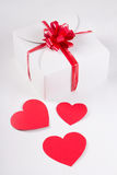 Gift box with red paper hearts over white. Background Royalty Free Stock Photo