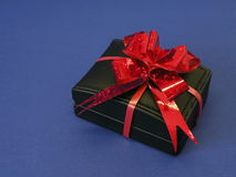 Gift box and red ribbon. Black leather gift box with red ribbon isolated on blue Stock Image