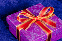 A gift box,with red ribbon, on blue Stock Photography