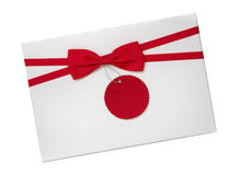 Gift box with red ribbon bow and paper tag top view isolated on white background, path Royalty Free Stock Photo