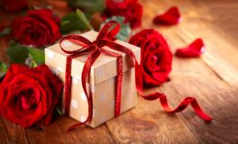 Gift box with red ribbon bow and red roses royalty free stock images