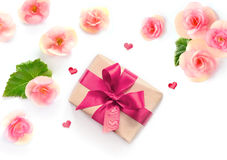 Gift box with red ribbon and bow on white with flowers background. flat lat, top view Stock Image