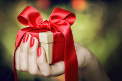 Gift box with red ribbon in hand Royalty Free Stock Photo