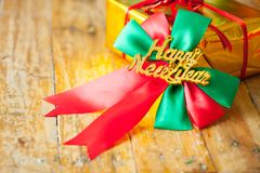 Gift box and red ribbon and Happy new year gift on wood b Royalty Free Stock Photo