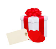 Gift box with red ribbon, hearts and tag (label) isolated. On white background Royalty Free Stock Images