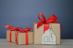 Gift box with red ribbon and house model with keys on black bac stock photo
