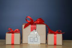 Gift box with red ribbon and house model with keys on black background, Gift new home and Real estate concept stock photos