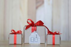 Gift box with red ribbon and house model with keys on wooder background, Gift new home and Real estate concept stock photography