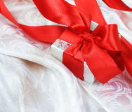Gift Box with Red Ribbon over Silk Royalty Free Stock Image