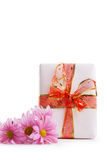 Gift box with red ribbon and pink dasies Royalty Free Stock Photography