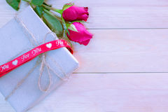 Gift box. With red ribbon and red rose flower on wooden background for valentine decoration Royalty Free Stock Photo