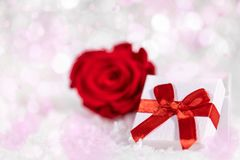 Gift box with red ribbon and rose blossom, pink and white backgr Royalty Free Stock Photo