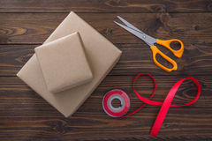 Gift box with red ribbon and scissors on wooden table Royalty Free Stock Photos