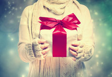 Gift box with red ribbon in the snowing night Stock Images