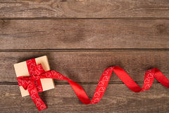Gift box and red ribbon with tag on wood background  space. Stock Photos