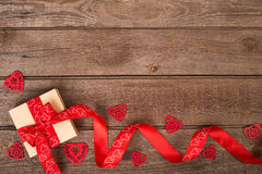 Gift box and red ribbon with tag on wood background  space. Stock Image