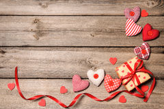 Gift box with red ribbon with textile hearts Stock Photos