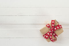 Gift box with red ribbon on white painted wooden planks and empt Royalty Free Stock Photography