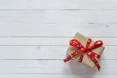 Gift box with red ribbon on white painted wooden planks and empt. Y space for text. Top view with copy space Stock Photos