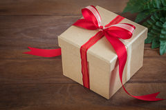Gift box with red ribbon on wooden background Stock Photos