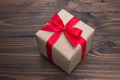 Gift box with red ribbon on wooden table for valentines day Stock Photos