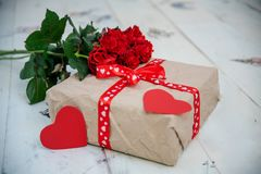 Gift box and rose flowers on light wooden background royalty free stock images