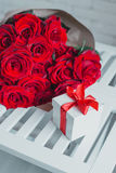 Gift box and red roses. Present on Valentine's Day for woman Royalty Free Stock Photo