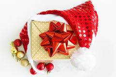 Gift box with a red Santa hat and sparkle ball Stock Photos