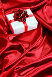 Gift box on red satin background Royalty Free Stock Photos