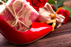 Gift box and red shoe. Roses near footwear on wood. Original way to give present. How to congratulate women Stock Photo