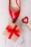 Gift box and red shoe. Small heart on wooden background. Congratulate your girlfriend. Present for a stylish lady Stock Images