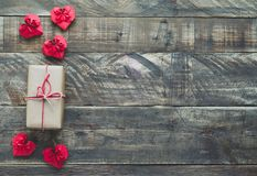 Red paper hearts with gift on wooden background, Valentines Day. Gift box with Red Valentine`s hearts on wooden bottom. Overhead plane with space to write Stock Image