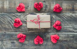 Red paper hearts with gift on wooden background, Valentines Day. Gift box with Red Valentine`s hearts on wooden bottom. Zenithal plane Royalty Free Stock Image